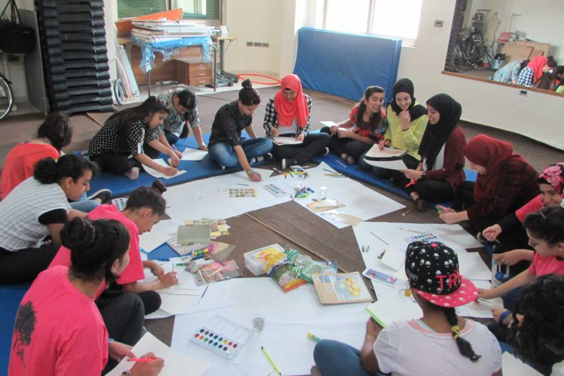 Fifteen young women sitting in circle on floor working on art projects