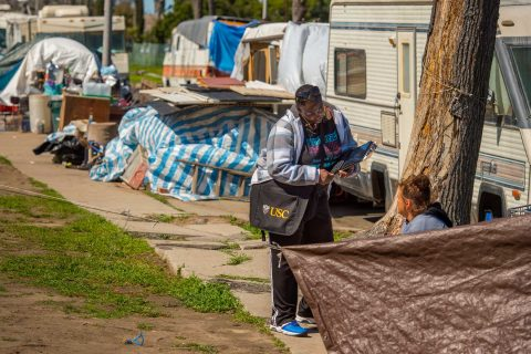 Woman speaking to homeless person with tents in background