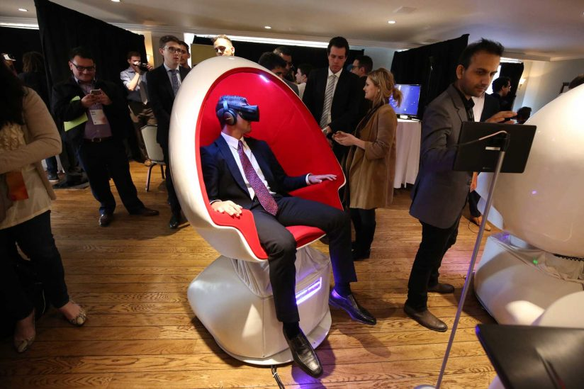 Man in suit and tie sitting in chair with VR headset
