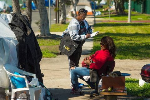 woman standing interviewing seated homeless woman in neighborhood on a lawn