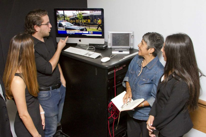 four people looking at tv screen discussing picture