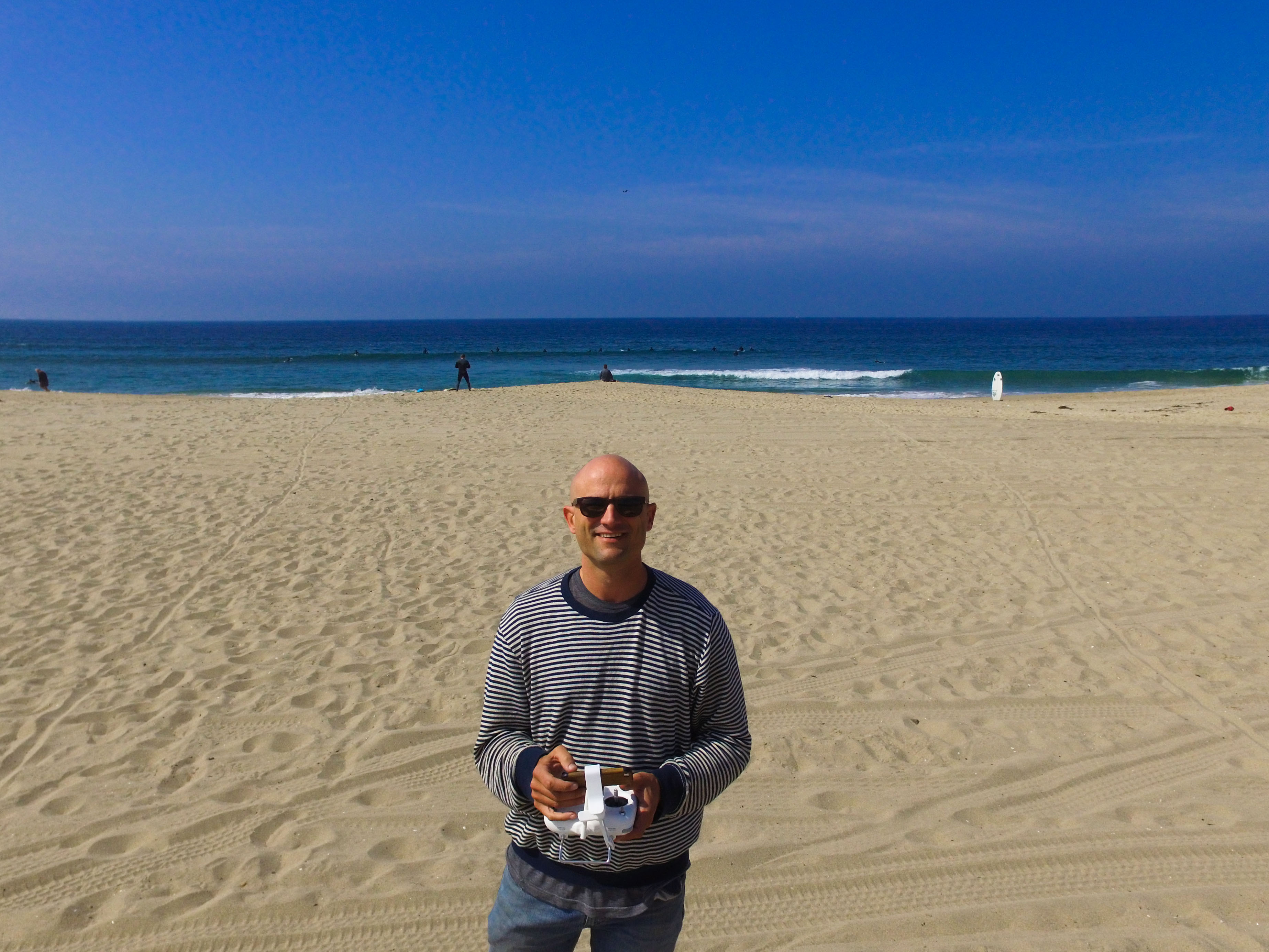 Portrait of Keith Plocek at the beach flying a drone