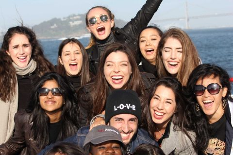 Ten students pose in group photo aboard boat in bay