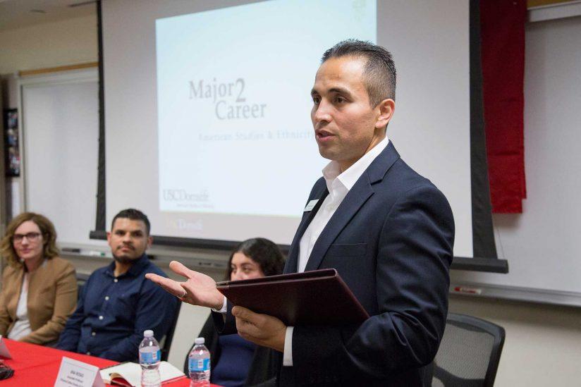 Octavio Avila speaking in front of class