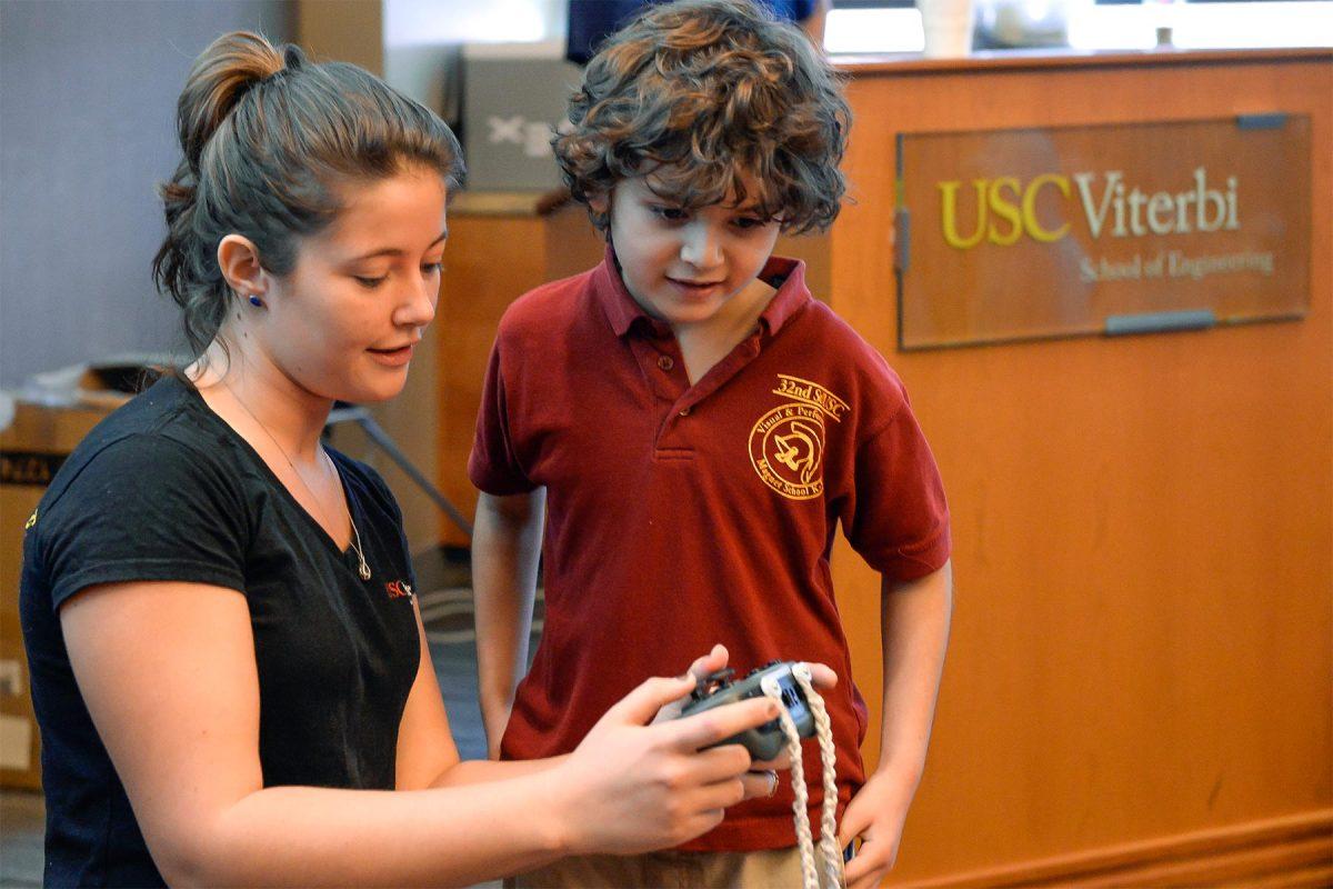 USC student Kiera Salvo shows Elias Rojano how to control the Vex U robot.