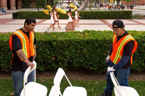 workers setting up chairs while graduating students walk by