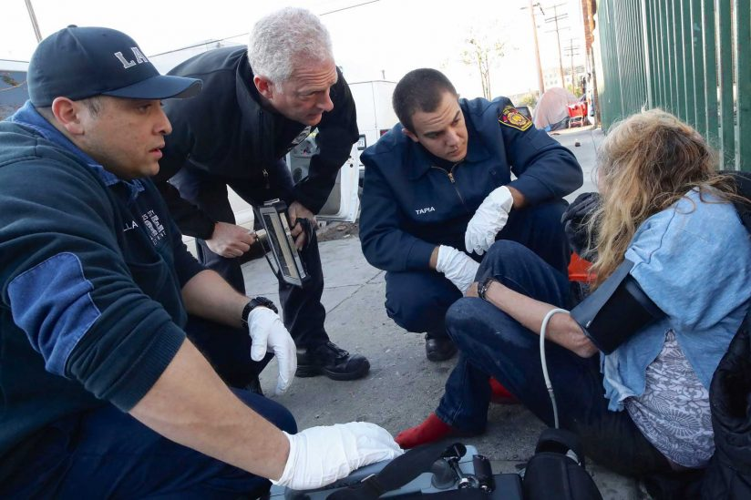 Three firemen checking in on a woman sitting on the sidewalk