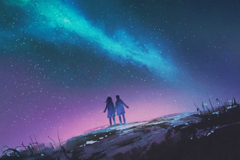 two people silhouetted against night sky and milky way galaxy