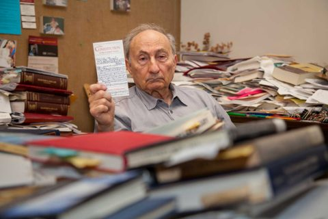 Michael Shapiro in his office holding up pocket copy of constitution