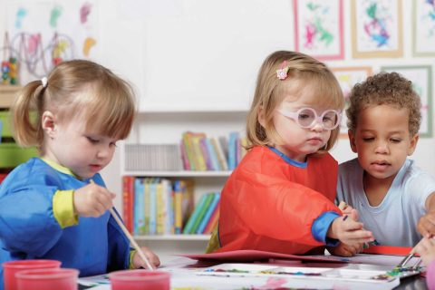 group of three toddlers doing crafts, one with glasses