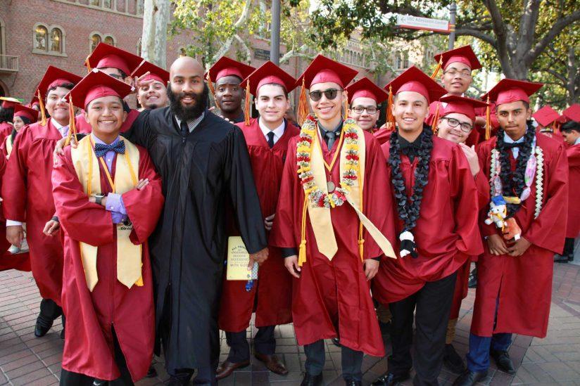 Group of graduates celebrates with teacher