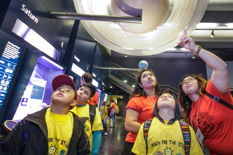 children looking up at display of Saturn pointed out by the adults