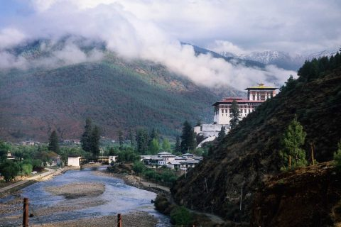 A monastery in the hills of Bhutan with clouds overhead