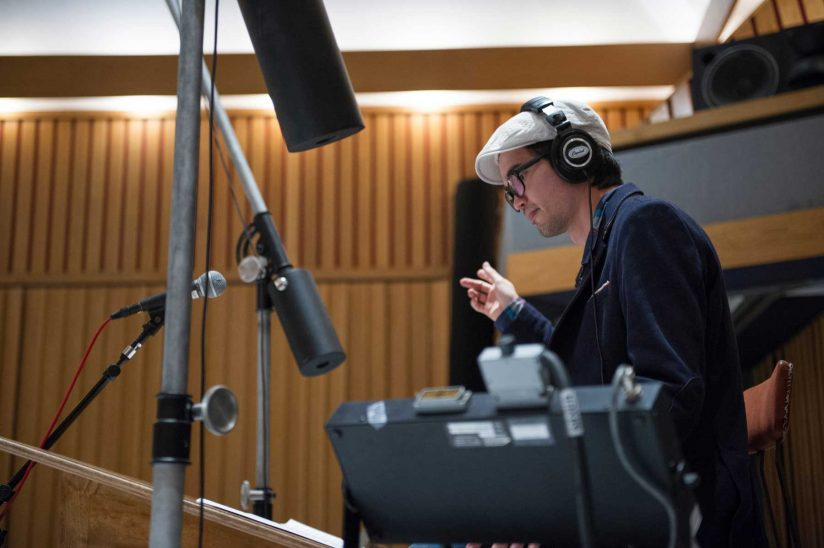 Musician with headphones conducting recording session with mics surrounding