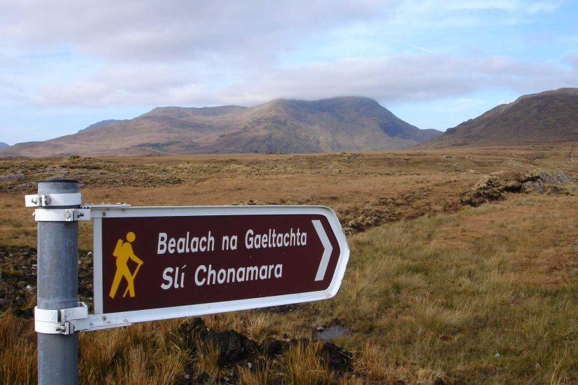 Hiking sign written in Gaelic in front of Irish landscape