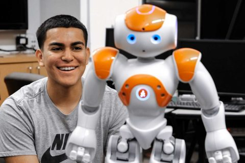 Omar Silva watches a robot which is standing on a table