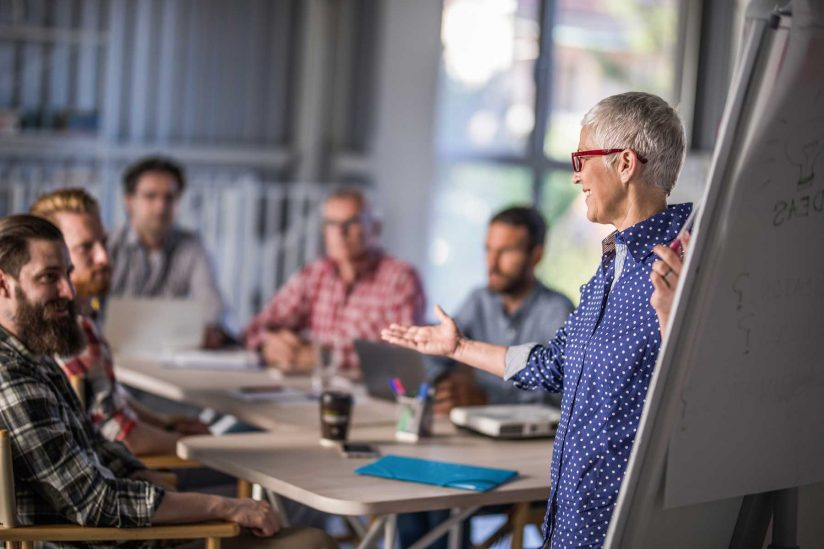 Older woman giving presentation to group of men in the workplace