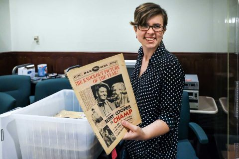 Rebecca Stimson holding old newspaper