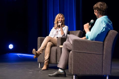 Lisa Kudrow onstage in chair sitting opposite David Bridel