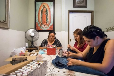 Three women sitting around a table sewing and working on designs