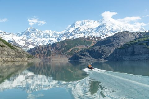 boat in glacial waters driving toward mountain
