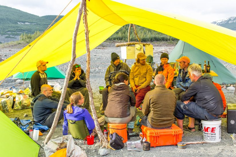 team sitting under a tarp having a camp discussion