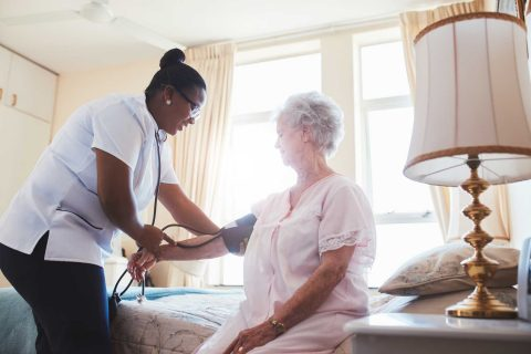 nurse checking on elderly patient