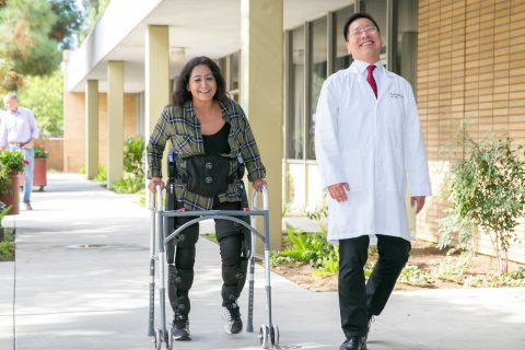 Cynthia Ramirez walking with aid of exoskeleton, accompanied by Charles Liu