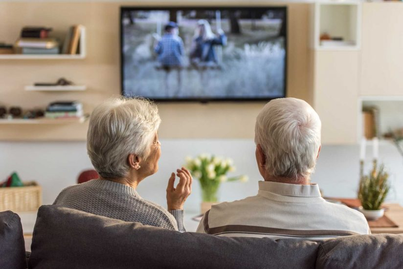 senior couple watching television