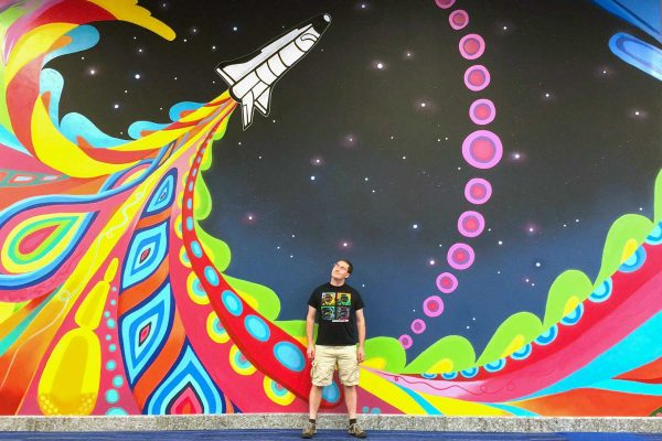 Joshua Fogel in front of mural