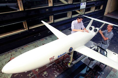 Two people work on a model plane inside a wind tunnel