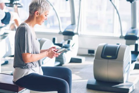 Senior woman using phone at gym