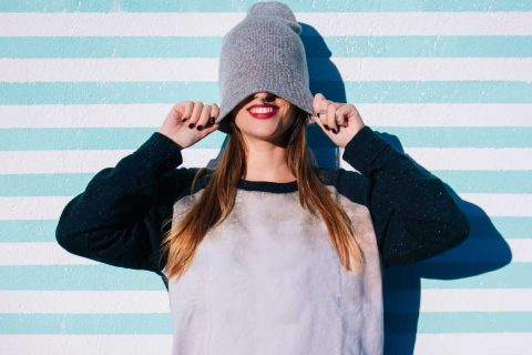 Girl pulling woolen hat over eyes