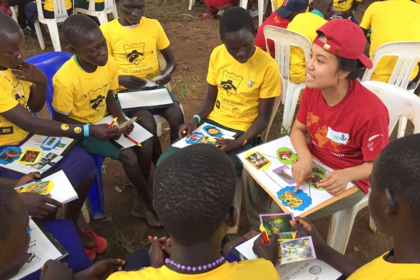 Kim Tran surrounded by schoolchildren in Uganda