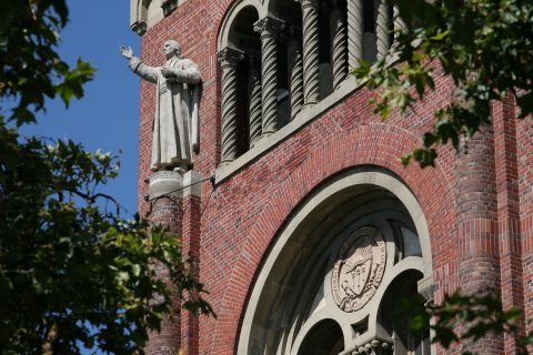 A statue of John Wesley stands guard atop Bovard Administration Building on the USC University Park Campus