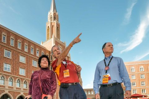 Three people touring USC Village with clock tower in background