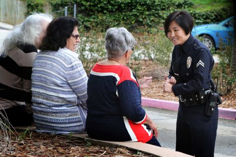 Female Asian LAPD officer talks to three women who are sitting down