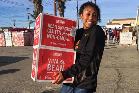 Student-athlete Mecca McGlaston helps organize boxes of food.