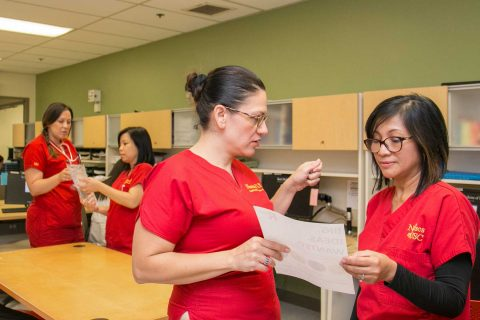 Norris nurses wearing red scrubs in office, talking