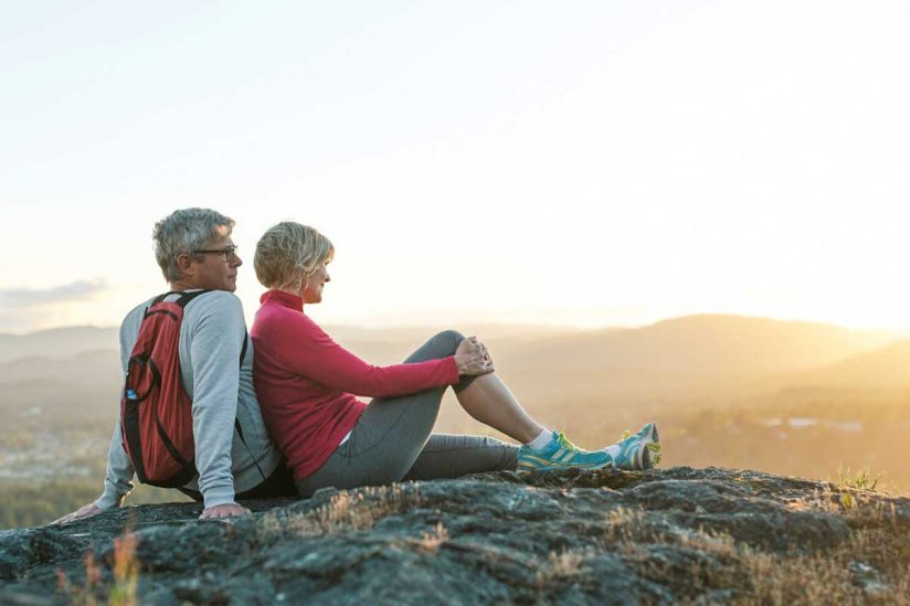 Middle-aged couple exercising looking out at sunset in nature