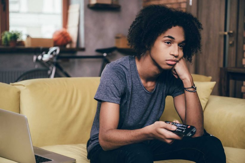 Young man watching TV, illustrating story that binge-watching can be bad for you