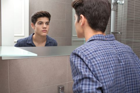 teenage man looking into mirror