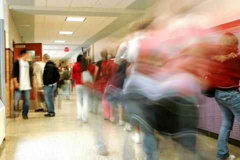 motion blurred students walking down school hallway