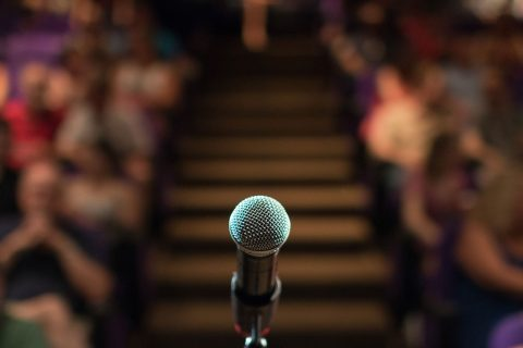 public speaking on stage illustrated by microphone in front of audience