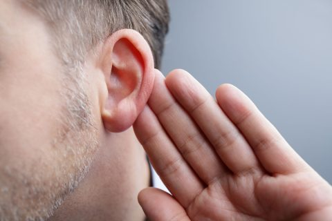 man listening and motioning toward ear