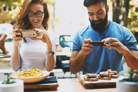 couple taking photos of food on phone