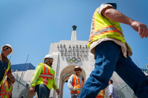 L.A. Coliseum renovation: workers pass the peristyle