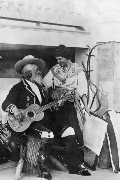 Don Antonio Coronel plays a guitar as his daughter, Dona Mariana Coronel stands by his side