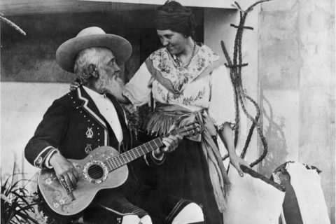 Don Antonio Coronel playing a guitar as Dona Mariana Coronel stands by his side