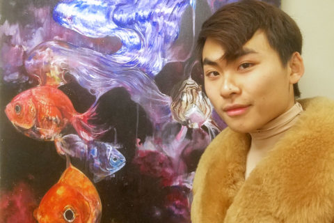 "Student artist Brian Dinh with his first oil painting, ""Dream Beam,"" which is on display in USC's Office of the Provost. (USC Photo/Chandrea Miller)"